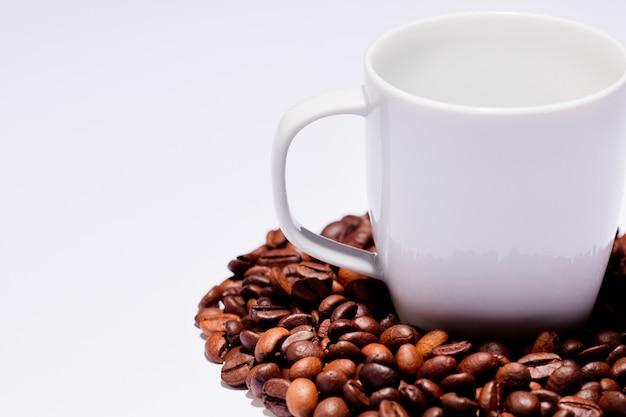 Geïsoleerde koffiebonen met ceramische kop, wit.