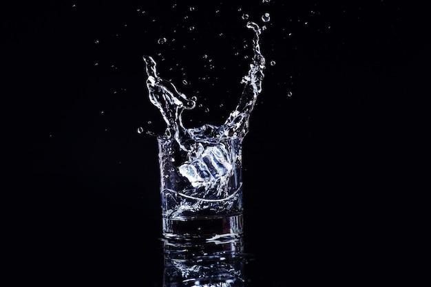 Geïsoleerde koud water in een glas met splash en blokjes ijs op zwart, cognac in een glas