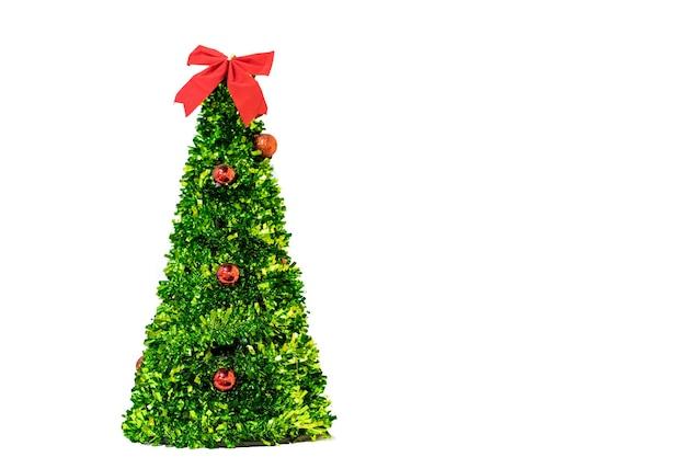 Geïsoleerde kunstmatige groene kerstboom met rode ballen en boog kopie ruimte