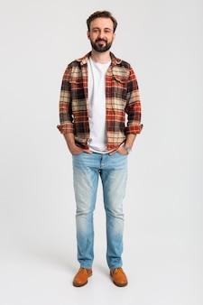 Geïsoleerde lachende knappe bebaarde man in hipster outfit gekleed in spijkerbroek