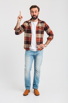 Geïsoleerde lachende knappe bebaarde man wijzende vinger met idee in hipster outfit gekleed in spijkerbroek