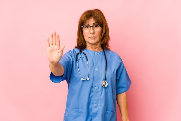 Geïsoleerde middelbare leeftijd blanke verpleegster vrouw staande met uitgestrekte hand tonen stopbord, waardoor u.