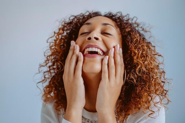 Geïsoleerde mooie vrouw wat betreft haar gezicht. vrolijke vrouw met witte tandarts glimlach. portret van afro-amerikaanse jonge vrouw met een perfecte gladde huid. huidverzorging en schoonheid concept. afro levensstijl.
