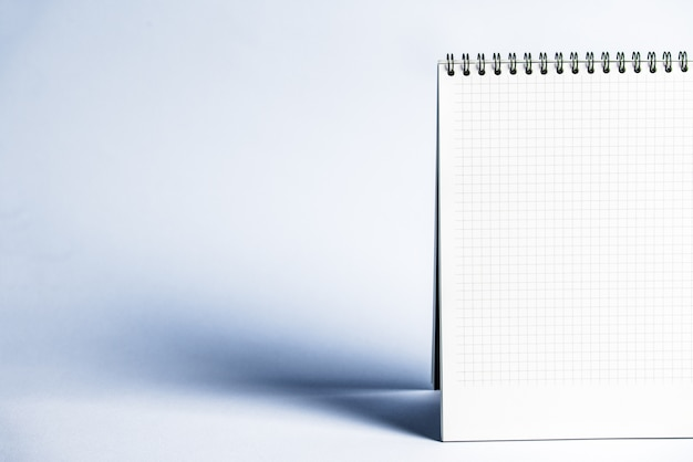 Geïsoleerde notitieboekje met spiraal op de grijsblauwe achtergrond