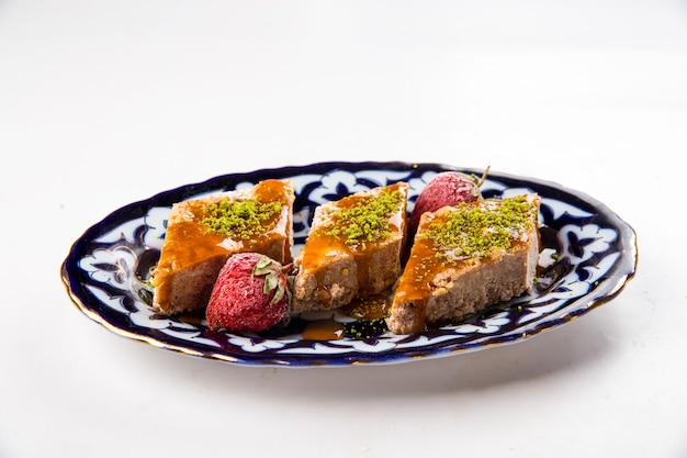 Geïsoleerde oosterse zoetheid baklava met honing en pistachenoten op de traditionele plaat