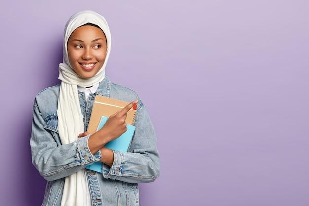 Geïsoleerde opname van tevreden moslimstudent toont geweldige advertentie, wijst naar de rechterbovenhoek, draagt witte sluier en spijkerjasje
