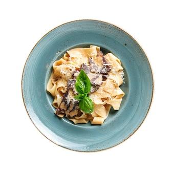 Geïsoleerde plaat van pappardelle pasta met vlees en kaas