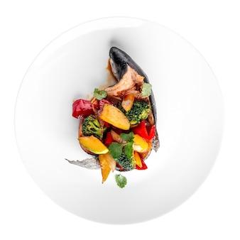 Geïsoleerde plaat van vis gevuld met groenten