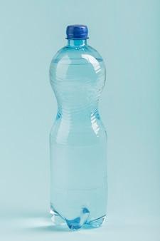 Geïsoleerde plastic fles water op blauwe achtergrond