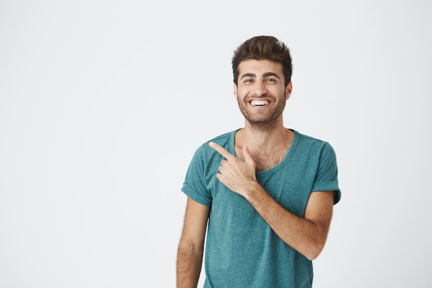 Geïsoleerde portret van gelukkig aantrekkelijke blanke man in casual blauw t-shirt, met trendy kapsel, glimlachend en wijzend op blinde muur. kopieer ruimte.