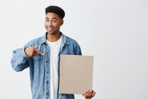 Geïsoleerde portret van jonge knappe donkere man met afro kapsel in wit t-shirt onder spijkerjasje met karton in de hand, wijzend op het met vrolijke en enthousiaste uitdrukking