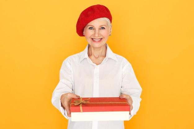 Geïsoleerde portret van mooie gelukkige senior blanke vrouw in elegante kleding poseren op geel