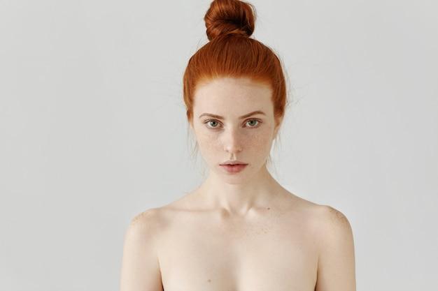 Geïsoleerde portret van mooie jonge blanke roodharige vrouw met haar broodje en perfect schone huid met sproeten staan op grijze muur met blote schouders
