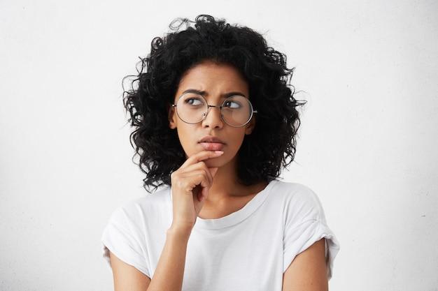 Geïsoleerde portret van stijlvolle jonge gemengd ras vrouw met donker ruig haar haar kin aan te raken