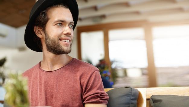 Geïsoleerde portret van vrolijke jonge bebaarde hipster glimlachend en plezier tijdens een leuk gesprek met zijn vrienden