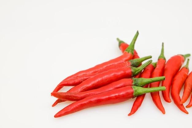 Geïsoleerde rode chillis op wit.