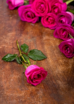 Geïsoleerde roze rozen bloeien op een houten tafel