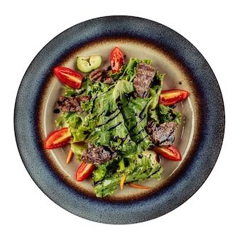 Geïsoleerde salade met warm kalfsvlees en groenten