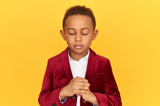 Geïsoleerde schot van afro-amerikaanse kleine jongen die de ogen bedekt en vuist knijpt, diep probeert te ademen om te kalmeren, zijn geduld verliest, boos en woedend is.