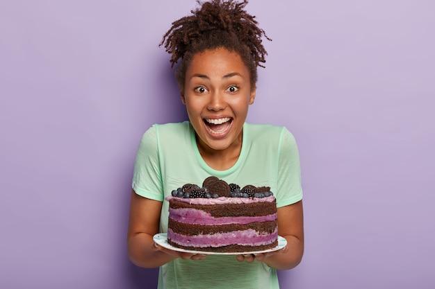 Geïsoleerde schot van dolblij afro huisvrouw blij om heerlijke bosbessencake te bakken