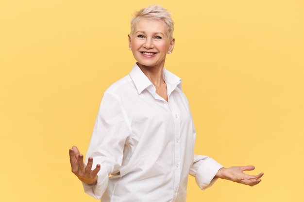 Geïsoleerde schot van dolblij succesvolle volwassen vrouw baas in wit overhemd hand in hand wijd uit elkaar en glimlachend gelukkig, motiverende toespraak geven, medewerkers energie geven, haar houding uiten vertrouwen