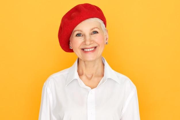 Geïsoleerde schot van gelukkig goed uitziende positieve vrouw van middelbare leeftijd met kort haar poseren tegen een gele achtergrond, gekleed in een rode motorkap en een wit overhemd, kijkend naar de camera met een vrolijke brede glimlach