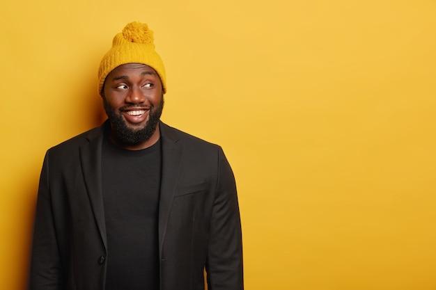 Geïsoleerde schot van gelukkige afro-amerikaanse man kijkt weg met blije uitdrukking, glimlacht breed, draagt wintermuts met pompon, zwart pak, geïsoleerd op gele studiomuur