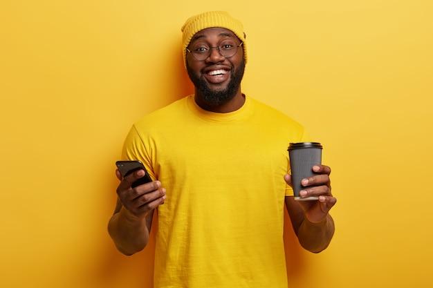 Geïsoleerde schot van gelukkige zwarte man in gele kleding, bericht typen, nieuwe applicatie downloaden op smartphone, koffie drinken uit een wegwerpbeker, brede glimlach, witte tanden, dikke haren.