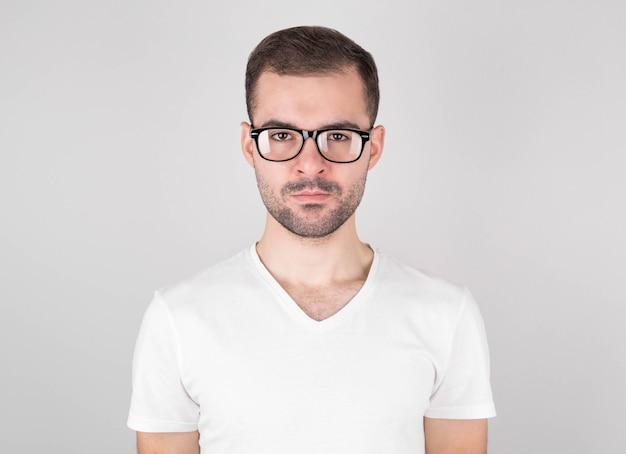Geïsoleerde schot van jonge knappe man met baard, snor en trendy kapsel, draagt casual grijze trui, heeft ernstige uitdrukking als luistert naar gesprekspartner, poseert in studio tegen witte achtergrond