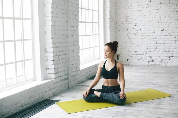 Geïsoleerde schot van mooie brunette jonge vrouw die sportkleding draagt ?? die yoga beoefent op fitnessmat, ogen sluit, benen gekruist houdt in lotus houding, met een rustige, vredige blik op haar gezicht
