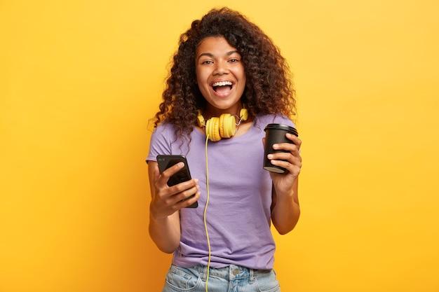 Geïsoleerde schot van opgetogen jonge vrouw met afrokapsel poseren tegen de gele muur