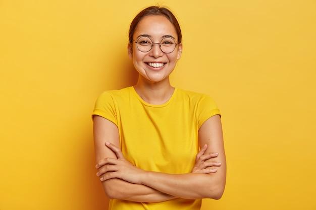 Geïsoleerde schot van tevreden vrolijke vrouw met oosterse uitstraling, breed glimlachend, in goed humeur, vermaakt door grappige vrienden, nonchalant gekleed, draagt een grote transparante bril, geïsoleerd op geel