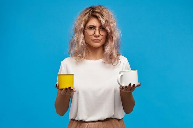 Geïsoleerde schot van twijfelachtige onzekere aantrekkelijke jonge vrouw, gekleed in stijlvolle kleding met witte kop warme chocolademelk of cacao en gele mok met warme melk, aarzelend
