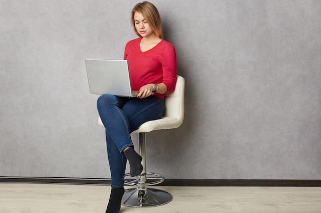 Geïsoleerde schot van vrij ernstige blonde vrouw geconcentreerd in laptopcomputer, zit aan witte fauteuil, gekleed in rode trui en spijkerbroek, vormt over grijze muur, verbonden met draadloos internet, werkt freelance