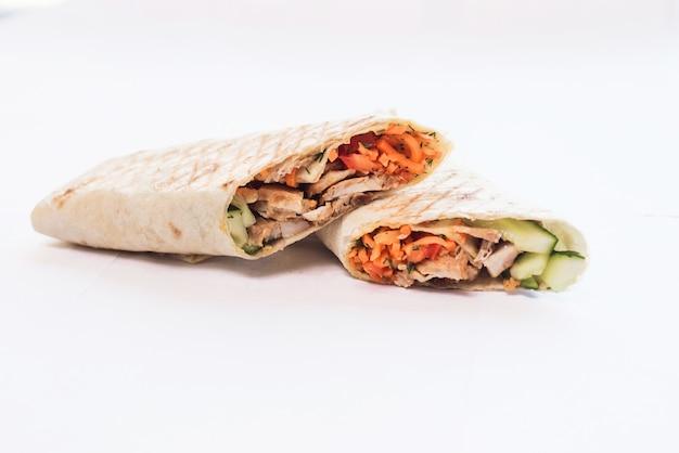 Geïsoleerde shoarma met een schaduw. oosters eten gemaakt van kippenvlees, tomaten, komkommers in pitabroodje
