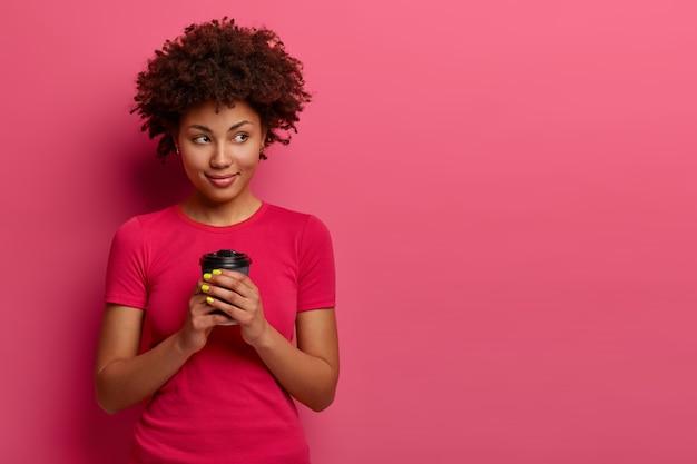 Geïsoleerde shot van aantrekkelijke gekrulde vrouw houdt afhaalkoffie vast, kijkt opzij en denkt aan iets terwijl ze drinkt, geniet van vrije tijd en aangename gedachten, poseert tegen een roze muur met vrije ruimte