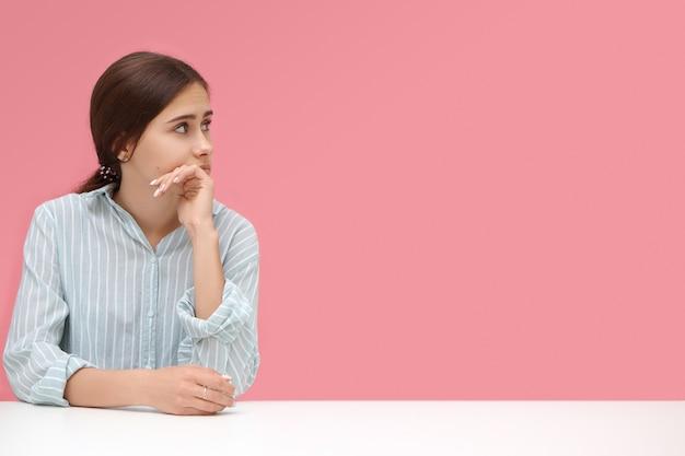 Geïsoleerde shot van aantrekkelijke jonge zakenvrouw die een blauw gestreept shirt draagt en aan haar bureau zit met de hand op haar kin, bedachtzaam kijkend op de lege roze muur met copyspace voor uw informatie