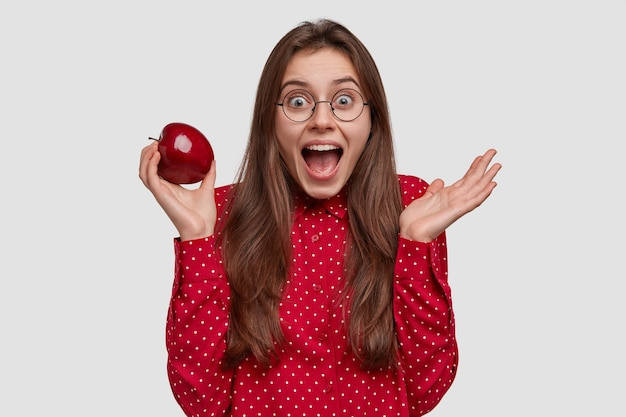 Geïsoleerde shot van aantrekkelijke vrouw heeft blije uitdrukking, houdt rode appel in de ene hand, drukt positieve gevoelens uit, draagt een formeel overhemd