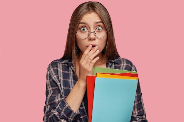 Geïsoleerde shot van bang jonge vrouw poseren tegen de roze muur met bril