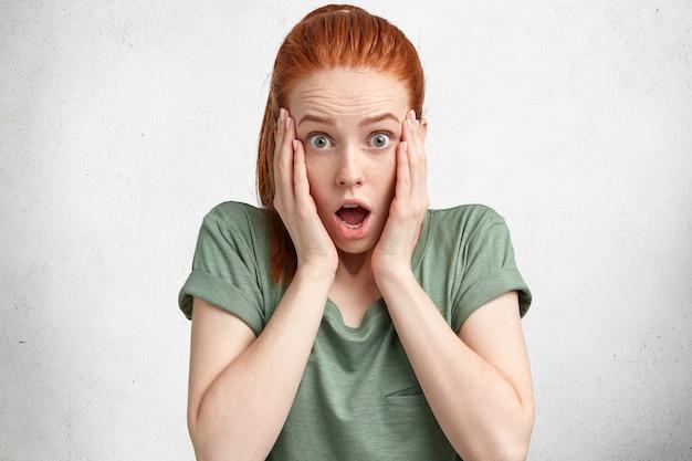 Geïsoleerde shot van bange emotionele vrouw met rood haar, houdt de handen op de wangen, voelt zich geschokt als iets vergeet, gekleed in een casual wit t-shirt, geïsoleerd over wit