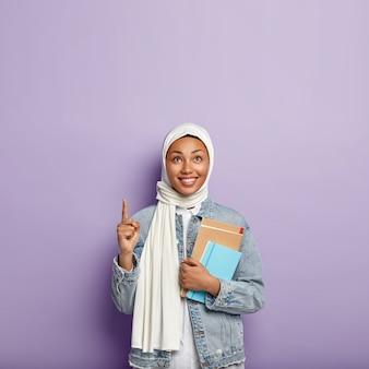 Geïsoleerde shot van blij religieuze vrouw bedekt hoofd met sluier, draagt blocnote, wijst met wijsvinger naar boven, glimlacht graag, staat over paarse muur, lege ruimte voor promotie. islamitische meisjesstudies