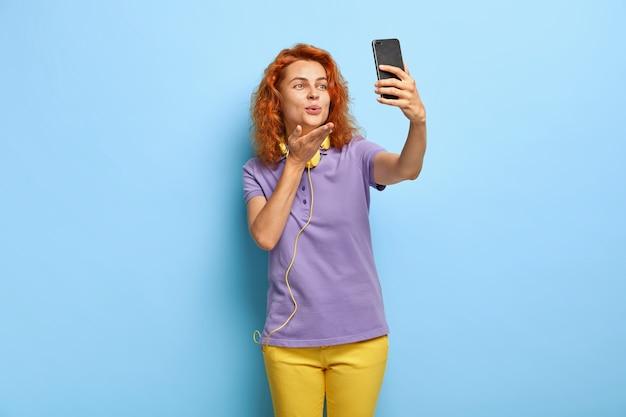 Geïsoleerde shot van charmante mooie gekrulde roodharige vrolijke vrouw zendt luchtkus op camera van mobiele telefoon