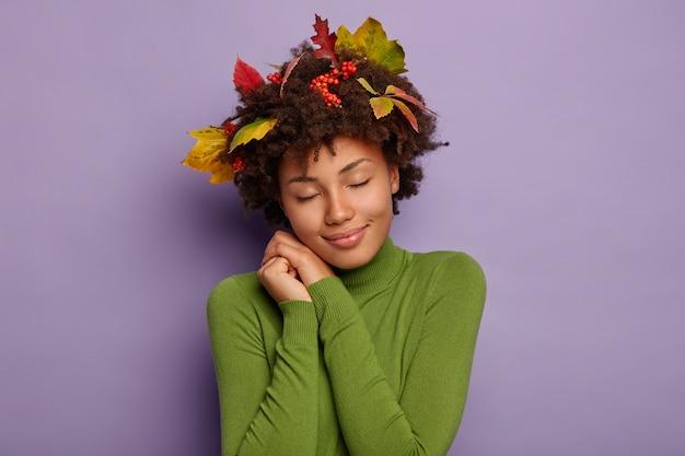 Geïsoleerde shot van charmante vrouw leunt naar handen, heeft ogen dicht, draagt groene comfortabele coltrui, heeft herfstbladeren en bessen vast in het haar