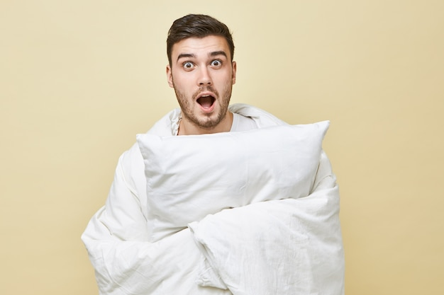 Geïsoleerde shot van doodsbange jonge, bebaarde man die zichzelf rolt in een witte deken en schreeuwt met wijd geopende mond, kan niet in slaap vallen vanwege enge film. bedtijd, slaap en slapeloosheid concept