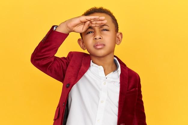 Geïsoleerde shot van een kleine afro-amerikaanse jongen met geconcentreerde gefocuste gezichtsuitdrukking die naar boven kijkt met de hand op het voorhoofd en fronsende wenkbrauwen, probeert iets duidelijker te zien