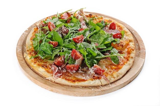Geïsoleerde shot van een pizza met ham en rucola