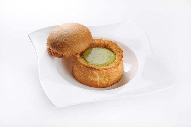 Geïsoleerde shot van een witte plaat met gebak met groene saus - perfect voor voedselblog of menugebruik