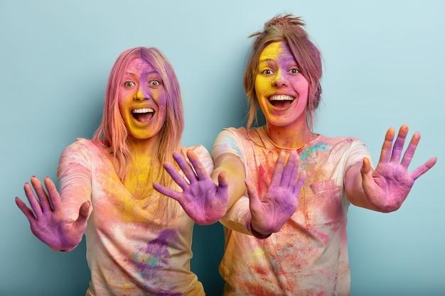 Geïsoleerde shot van emotionele gelukkige vrouwen strekken hun handen uit en tonen gekleurde handpalmen, lachen en hebben plezier binnen, vieren festival van kleuren, staan tegen een blauwe muur. holi-feest en feest