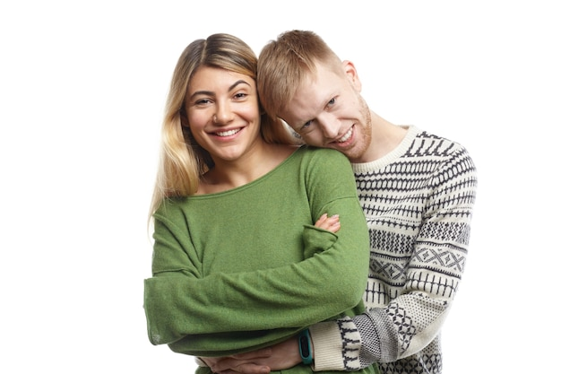 Geïsoleerde shot van gelukkig knappe jongen zachtjes omhelzen zijn schattige vriendin. stijlvol jong verloofd verliefde paar binnenshuis knuffelen, genieten van zoete momenten van hun geluk, vreugdevol glimlachen