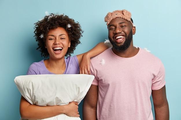 Geïsoleerde shot van gelukkige afro-amerikaanse man en vrouw lachen oprecht, genieten van een goede nachtrust, zacht kussen vasthouden, slaapmasker dragen, dicht bij elkaar staan, goede emoties uiten, binnenshuis poseren. beddengoed concept